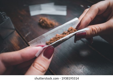 woman's hands preparing a tobacco for smoking on a wooden table with tobacco and a lighter