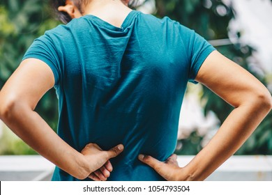 Woman's hands pressing against her lower back suggesting pain , office syndrome , health care concept