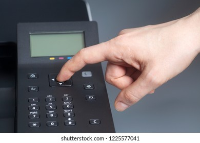 Woman's hands pressing button on color laser printer on gray