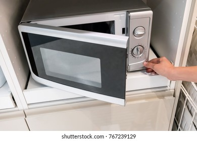 Woman's Hands pressing button to open microwave oven door