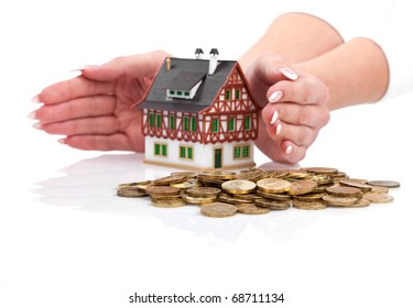 Womans hands protect miniature house with the coins.