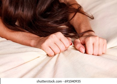 Woman's hands pulling white sheets in ecstasy, orgasm