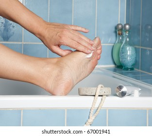 Woman's hands putting cream on callous feet