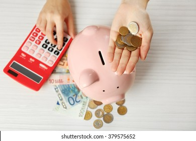 Woman's hands putting euro coin into a piggy bank and counting with calculator on the table. Financial savings concept