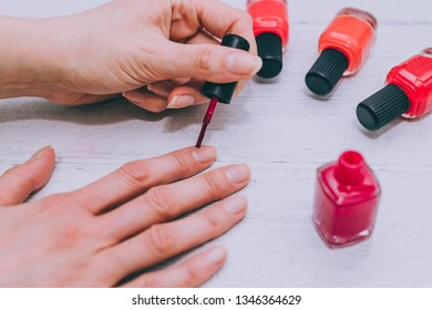 woman's hands with red nail polish bottle and other colors on wooden surface, concept of beauty indusry and cosmetics