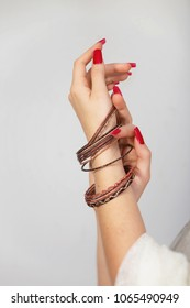 Womans hands with red nails and shiny bracelets. Close view.