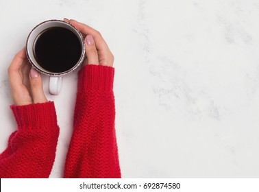 Woman's hands in a red sweater holding a cup of coffee, top view