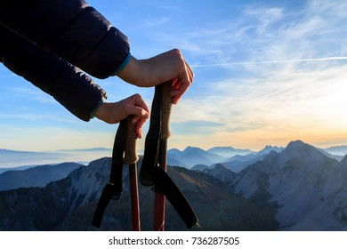 Womans hands resting on trekking poles on the top of the mountain