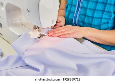 Woman's hands sew on a sewing machine close up