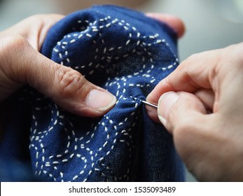 Woman's hands sewing running stitch in blue cloth. Japanese sewing pattern call Sashiko Patterns.