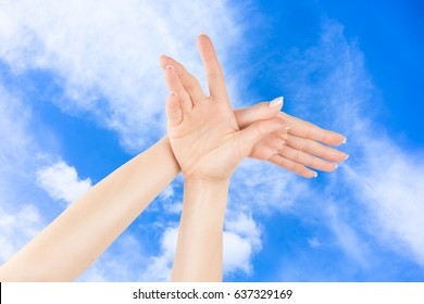 Woman's hands in the shape of bird on cloudy blue sky background for freedom, health and relax concept
