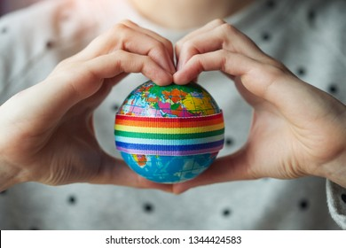woman's hands in shape of heart holding globe with LGBT rainbow ribbon, lesbian, gay couple and love concept, LGBT marriage