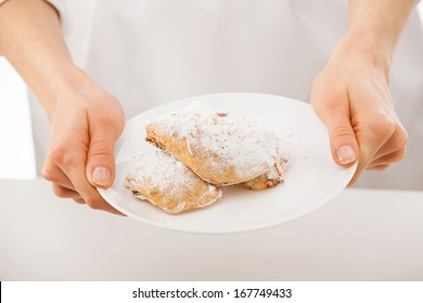 Woman's hands showing plate with strudels, closeup shot