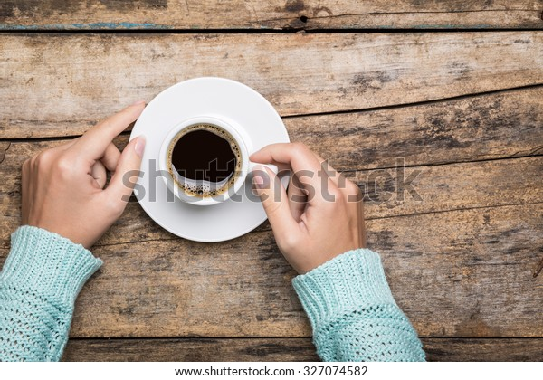 Woman's hands in sweater hold a cup of strong coffee on wooden table. Coffee fan top view background  with copy space