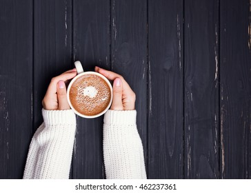 Woman's hands in sweater holding cup of coffee on the black wooden table