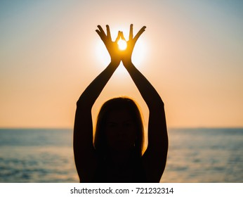 Woman's hands symbolizing prayer and gratitude. Mudra. Yoga concept. Silhouette of female hands on sun background. Beautiful scene