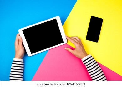 Woman's hands with tablet computer and smartphone on colorful background.
