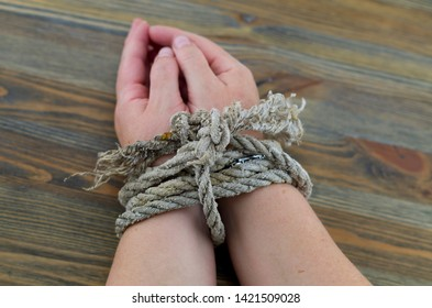 Woman's hands tied with an old rope, the rope is gray with age and unraveling at the ends. It is possible to interpret the picture as torture or as a tie for the time being.