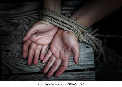 Woman's hands tied with rope lying on a wooden board.
