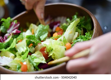 Woman's hands tossing fresh garden salad in a stylish wooden bowl