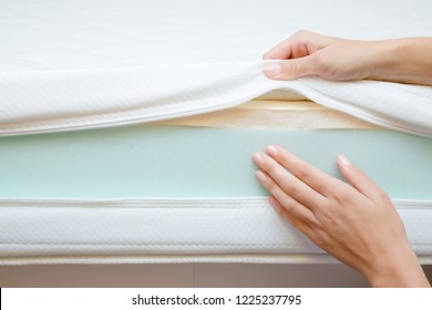 Woman's hands touching different layers of new mattress. Checking hardness and softness. Choice of the best type and quality. Front view. Close up.