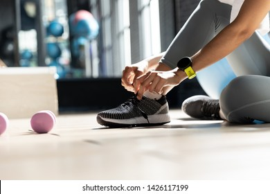 Woman's hands tying shoes Get ready to exercise at gym In a room with a window with natural light. Fitness and healthy lifestyle, Starting to exercise concept
