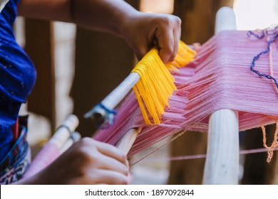 Woman's hands in typical Guatemalan dress weaving with colored threads in the weaver - indigenous artisan woman from Guatemala making local weaving in a rural area