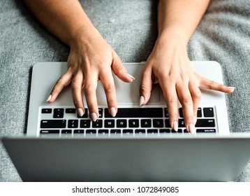 Woman's hands typing on a laptop computer from above