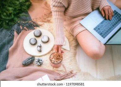 Woman's hands typing on laptop keyboard. Study and work online. Warm pink sweater, winter, home comfort and relax. Workspace with laptop, girl's hands, cake, cristmas gifts on white blanket.
