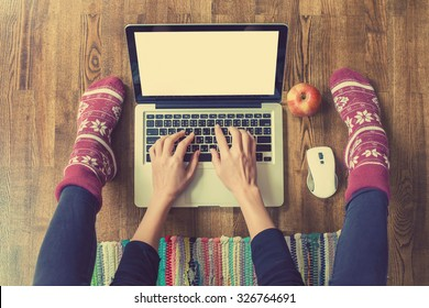 Woman's hands typing on laptop keyboard. Study and work online, freelance, warm socks, winter, home comfort and relax