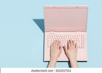Woman's hands typing on a pastel pink keyboard of retro laptop. Work and technology.