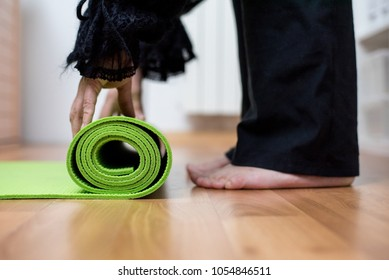 Woman's hands unrolling or rolling green yoga mat before or after her yoga practice. Exercise, healthy life concept.