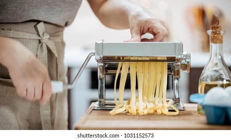 Woman's hands use a pasta cutting machine.