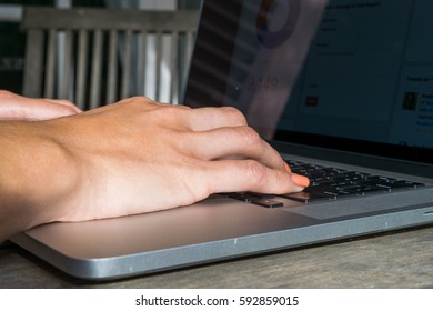 Woman's hands using laptop with analytical graph on desk in the garden, work on fresh air