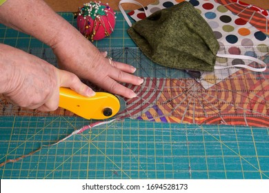 Woman's hands using a rotary cutter to cut leftover quilting fabric for hand sewn face masks