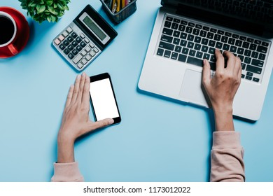 Woman's hands using smart phone and calculator,book,pen,mouse,cup of coffee,laptop computer  on modern blue desk table at office.