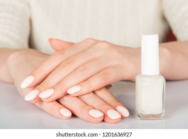 woman's hands with white nail varnish bottles. Nails care