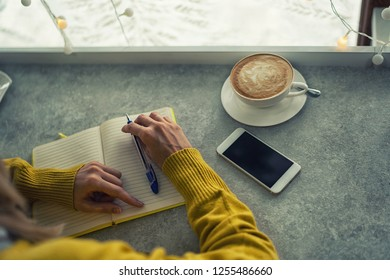 Woman's hands writing plans in notes while having a coffee break at the coffee shop table. Woman hand with pencil writing on notebook at coffee shop. Woman working in outdoor at coffee shop.