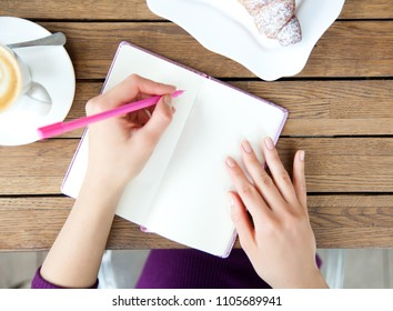 Woman's Hands writting at notebook in cafe. Top view, flat lay of blogger's work and rest