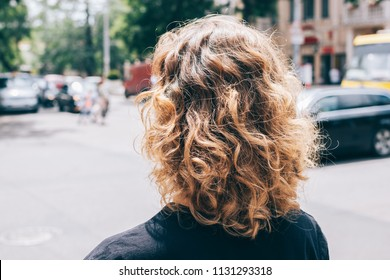 Woman's head with curly brown hair, back view. Close-up unrecognizable girl goes away at sunny summer day in the city.