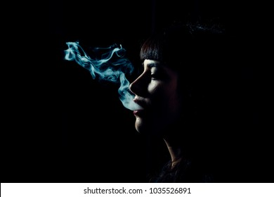 Womans head with smoke in mouth on black background. Side view and shape of female face and smoke. Smoke clouds come out of female lips, copy space. Smoking woman concept.