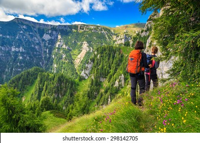 Woman's hiking team with colorful backpacks walking on narrow trail,Bucegi mountains,Carpathians,Transylvania,Romania,Europe