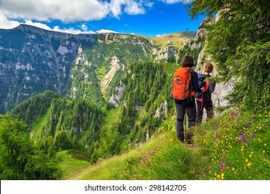 Woman's hiking team with colorful backpacks walking on narrow trail,Bucegi mountains,Carpathians,Transylvania,Romania,Europe