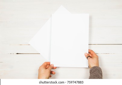Woman's holding a blank piece of paper over a wooden background