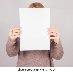 Woman's holding a blank piece of paper