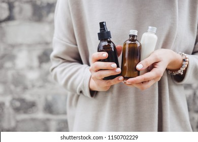 Woman's holding botles with spa cosmetics against gray wall.  Beauty blogger, salon therapy, minimalism concept, copyspace