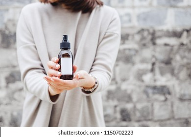Woman's holding brown glass bottle with spa cosmetics against gray wall.  Beauty blogging, salon therapy, product package, mockup, minimalism concept