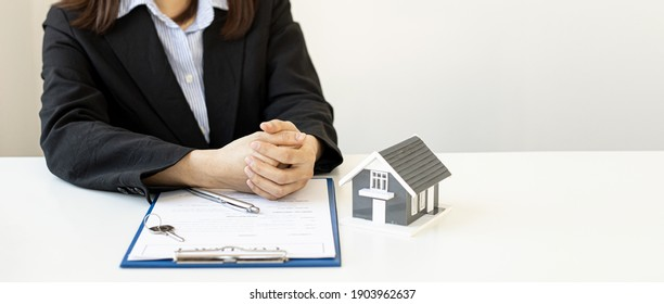 A woman's home salesperson discusses the details of the housing project to the client in the project sales office, on the table there is a gray miniature house model, real estate trading ideas.