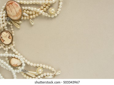 Woman's Jewelry. Frame with old vintage brooches, cameos, pearl beads, pearl earrings. Beautiful vintage jewelry on grey. Flat lay, top view