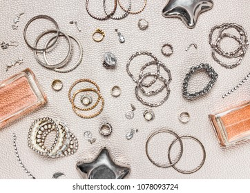 Woman's jewelry and perfume. Flat lay composition. Necklaces, earrings, rings, perfume bottles.